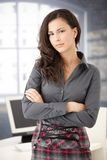 Pretty office worker standing in office smiling stock images