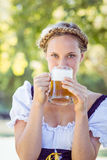 Pretty oktoberfest blonde drinking in the park Royalty Free Stock Images