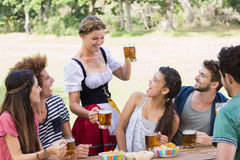 Pretty oktoberfest girl serving friends Stock Image