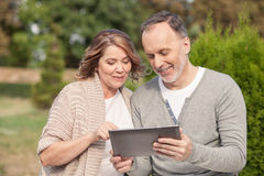 Pretty old husband and wife are using a tablet royalty free stock images