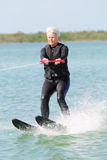 Pretty Older Lady Water Skiing. A pretty white haired older lady water skiing on a sunny day. Senior citizen wearing a black wet suit Stock Photo
