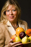 Pretty older woman in suit fruit bowl Royalty Free Stock Photos