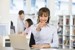 Pretty operator pointing a finger ,  headset, looking camera Royalty Free Stock Photo