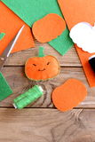 Pretty orange pumpkin ornament with eyes and mouth. Halloween crafts for kids. Top view. Halloween pumpkin made of felt, green thread, scissors, flat pieces of stock image