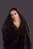 Pretty oriental woman in abaya on black background Stock Photography