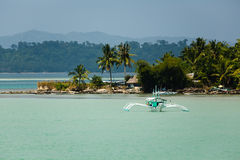Pretty outrigger boat approaches Tropical paradise in Philippines Stock Images