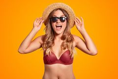 Pretty overjoyed female tourist keeps hands on summer hat, exclaims with happiness, has slim body, wears bikini, wears for beach s stock photos