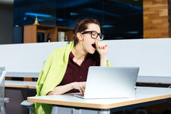 Pretty overworked businesswoman yawning and using laptop on workplace. Pretty overworked young businesswoman in glasses yawning and using laptop on workplace Stock Images