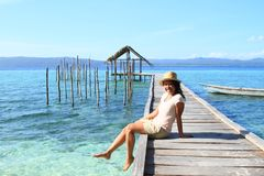 Tropical girl on jetty with shelter on sea stock photo
