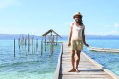 Tropical girl on jetty with shelter on sea royalty free stock photos