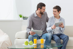 Pretty parent and child are using modern technology. Portrait of friendly family playing games on the tablet. The father and son are sitting on sofa and smiling Stock Photo