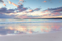 Pretty pastel dawn sunrise at Hyams Beach NSW Australia. The pretty pastel colours of dawn sunrise in the sky and clouds and reflections in the water at Hyams royalty free stock image