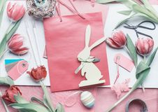 Pretty pastel Easter background with preparation of greeting with tulips flowers, eggs and bunny decoration Royalty Free Stock Photography