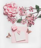 Pretty pastel pink greeting card mock up with blossom decoration, hearts, little gift box and bow on white desk background, top royalty free stock photos