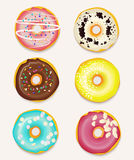 Pretty pastries background with chocolate, pink and banana color glace donuts. Stock Photos