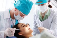 Oral treatment. Pretty patient having oral treatment in dental clinic Stock Images