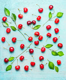 Pretty pattern made of sweet cherry with green leaves on light blue shabby chic background Royalty Free Stock Photo