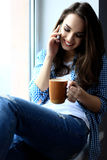 Pretty peaceful young woman using cell phone and Royalty Free Stock Photography