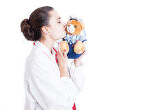 Pretty pediatric woman kissing teddy bear Stock Photo