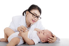 Pretty pediatrician checking a baby on studio Royalty Free Stock Images