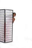 Pretty Peek-A-Boo Teen. Pretty African American teenage girl with bare shoulders peeking out from behind a gridded screen Stock Photo
