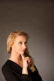 Pretty pensive caucasian blonde business woman looking into copy. Space stock images