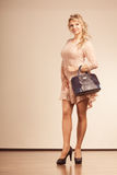 Pretty, pensively lady with black handbag. Stock Photos