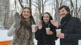 Pretty people waving hands in the winter snowy park stock video