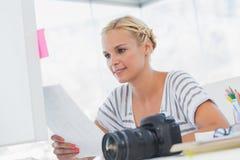Pretty photo editor looking at a contact sheet Royalty Free Stock Image