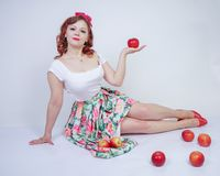 Pretty pin up caucasian young girl happy posing with red apples. cute vintage lady in retro dress having fun with fruits on white. Background alone. vegetarian stock image