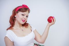 Pretty pin up caucasian young girl happy posing with red apples. cute vintage lady in retro dress having fun with fruits on white. Background alone. vegetarian royalty free stock photo