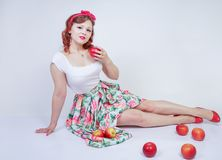 Pretty pin up caucasian young girl happy posing with red apples. cute vintage lady in retro dress having fun with fruits on white. Background alone. vegetarian stock photo