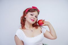 Pretty pin up caucasian young girl happy posing with red apples. cute vintage lady in retro dress having fun with fruits on white. Background alone. vegetarian stock photos