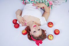 Pretty pin up caucasian young girl happy posing with red apples. cute vintage lady in retro dress having fun with fruits on white. Background alone. vegetarian stock photography