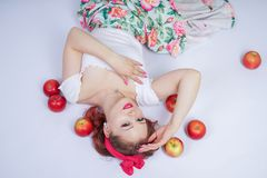Pretty pin up caucasian young girl happy posing with red apples. cute vintage lady in retro dress having fun with fruits on white. Background alone. vegetarian royalty free stock image