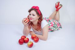 Pretty pin up caucasian young girl happy posing with red apples. cute vintage lady in retro dress having fun with fruits on white. Background alone. vegetarian royalty free stock photos