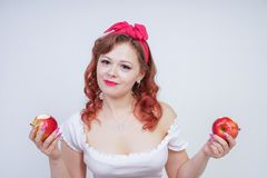 Pretty pin up caucasian young girl happy posing with red apples. cute vintage lady in retro dress having fun with fruits on white. Background alone. vegetarian stock images