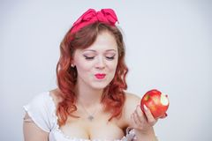 Pretty pin up caucasian young girl happy posing with red apples. cute vintage lady in retro dress having fun with fruits on white. Background alone. vegetarian royalty free stock photography