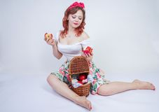 Pretty pin up caucasian young girl happy posing with red apples. cute vintage lady in retro dress having fun with fruits on white stock photo