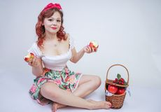 Pretty pin up caucasian young girl happy posing with red apples. cute vintage lady in retro dress having fun with fruits on white. Background alone. vegetarian royalty free stock images