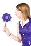 Pretty pin up girl playing with purple pinwheel Royalty Free Stock Images