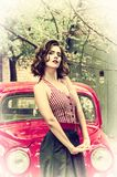 Pretty pin up girl posing on a red retro car background. Playful gaze fixed on camera. stock photography