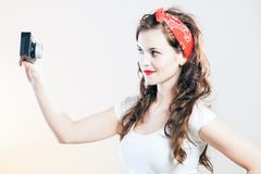Pretty pin up girl vintage camera taking picture Royalty Free Stock Photography