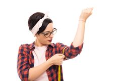 Pretty pin-up girl wearing glasses measuring her biceps royalty free stock photography