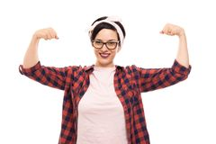 Pretty pin-up girl wearing glasses showing both her biceps. Portrait of young pretty pin-up girl wearing glasses showing both her biceps isolated on white royalty free stock image
