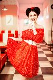 Pretty pin-up woman with make-up, vintage style. Pretty pin-up woman with make-up, red dress with white polka dots, vintage style. Retro cafe interior with Stock Images