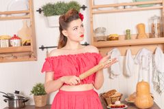 Beautiful young girl with flower in her hair posing in red pin up polka dot dress at home in the kitchen. Pretty pin up woman wearing red polka dot dress and royalty free stock photo