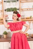 Beautiful young girl with flower in her hair posing in red pin up polka dot dress at home in the kitchen. Pretty pin up woman wearing red polka dot dress and royalty free stock photography