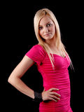 Pretty in Pink. Portrait of a beautiful blonde young woman smiling, wearing a pink dress on black background. Studio shot stock photos