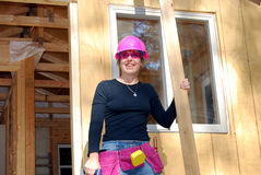 Pretty In Pink. Female carpenter with pink hard hat, toolbelt and safety glasses Royalty Free Stock Images